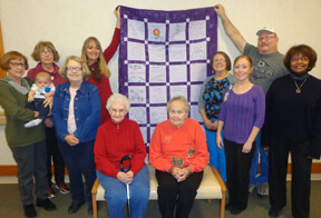 women holding cancer quilt